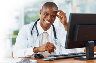 Happy doctor sitting at computer